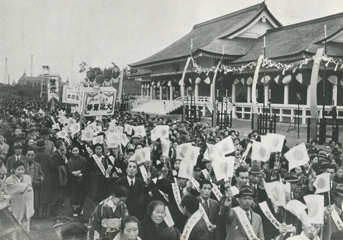 写真・図版 : 紀元2600年記念式典会場を旗行列で祝う人たち=1940年11月12日、東京市麹町区(現・東京都千代田区)