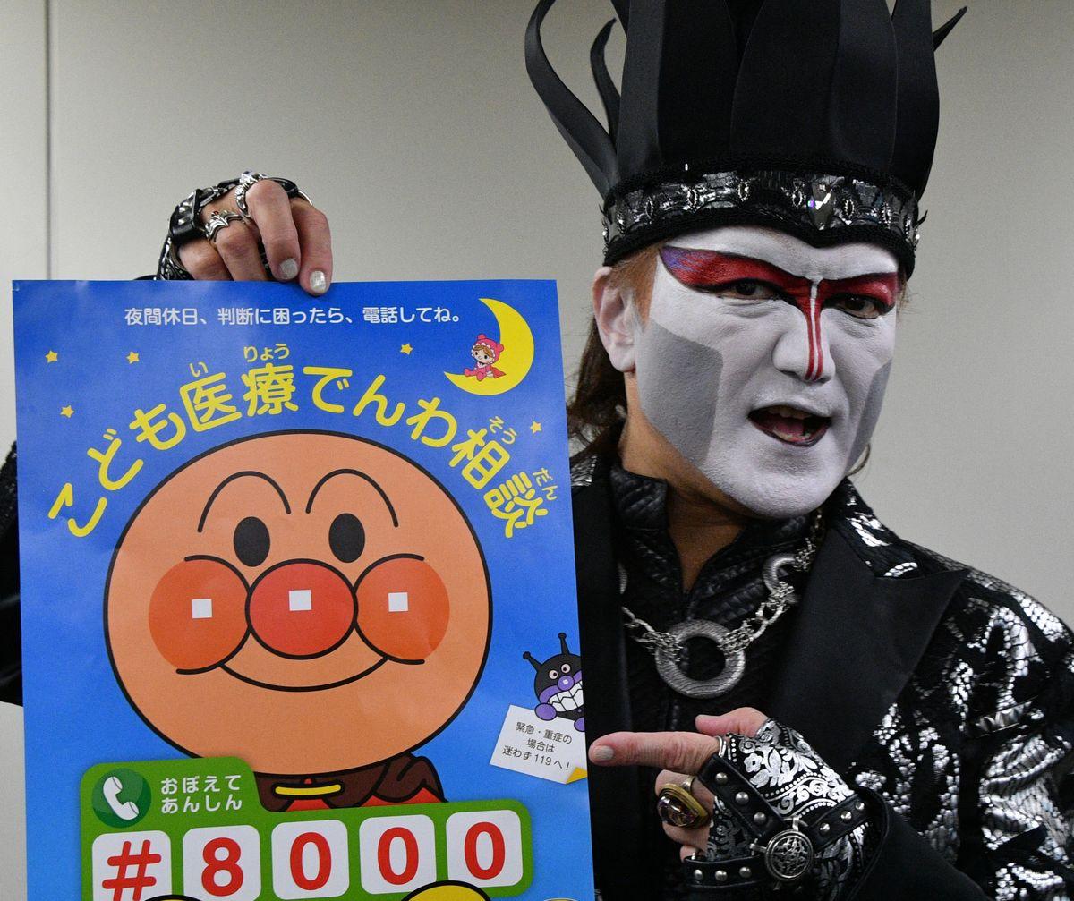 写真・図版 : 2018年、「こども医療でんわ相談」のポスターをPRするデーモン閣下さん=東京・霞が関。朝日新聞社