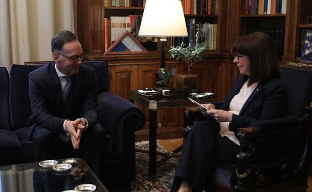 写真・図版 : ドイツの外相と会談するギリシャのサケラロプル大統領(右)=2020年7月21日、アテネ