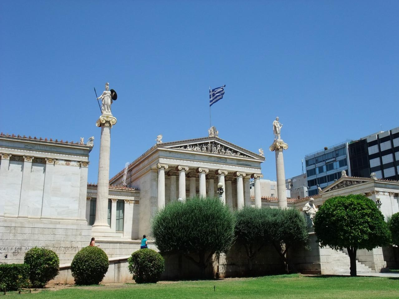 写真・図版 : ギリシャ学術院(アカデミア)。円柱の上には女神アテナと太陽神アポロンの像が青空に美しく映える。入口にはソクラテスとプラトンの像がある。古代ギリシャの偉人たちは名前のみだった