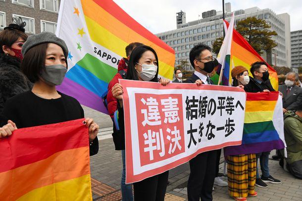 同性婚訴訟の判決後、「違憲判決」と書かれた紙を掲げる弁護士=2021年3月17日、札幌市中央区