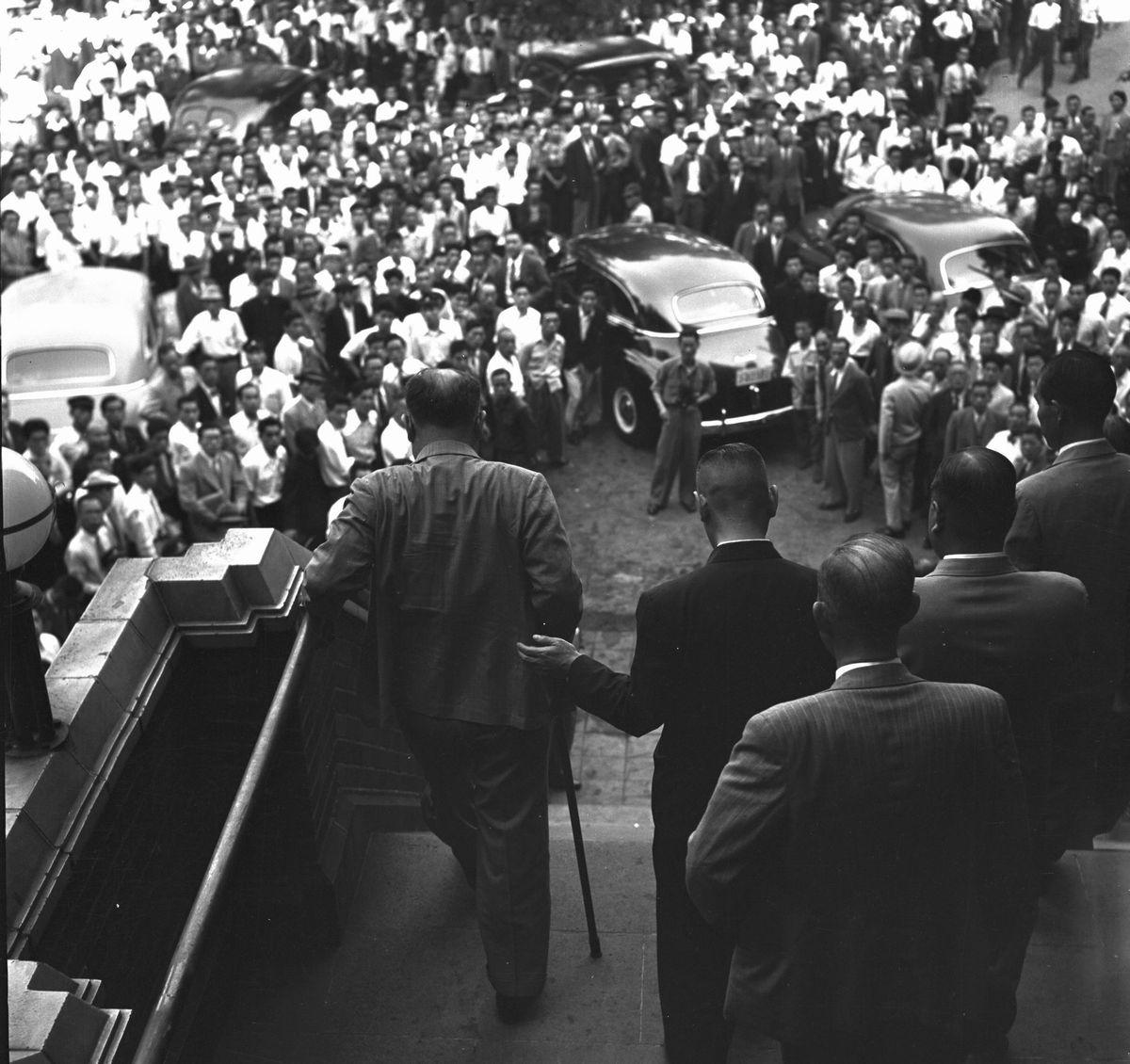 写真・図版 : 国民民主党、農民協同党、新政クラブなどで結成した保守政党「改進党」の臨時全国大会が東京・日比谷公会堂で開かれ、重光葵を初代総裁に選んだ。写真は杖をついて公会堂を出る重光新総裁を迎える群衆=1952年6月13日