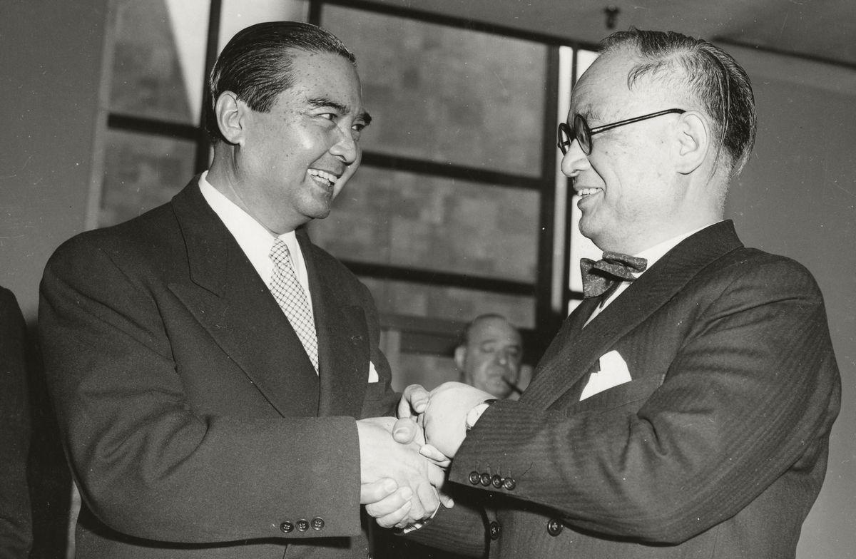 写真・図版 : 国連総会で、日本の加盟が全会一致で可決され、握手を交わす重光葵外相と国連総会議長のワン・ワイタヤコンタイ外相=1956年12月18日、米ニューヨークの国連本部