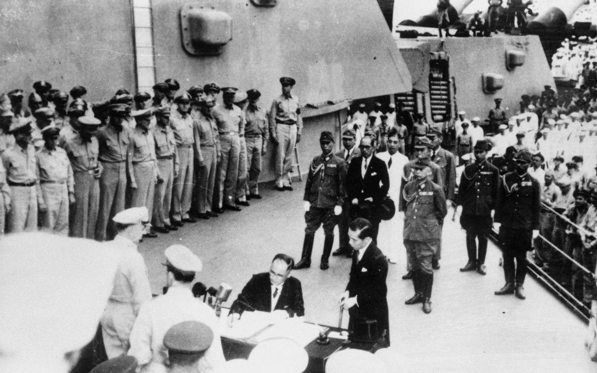 写真・図版 : 米戦艦ミズーリの艦上で、連合国軍最高司令官が提示した降伏文書に調印する日本の全権、重光葵外相。テーブルの手前、後ろ向き右がマッカーサー元帥。後方に並ぶのは各国代表。向こう側は日本代表団=1945年9月2日