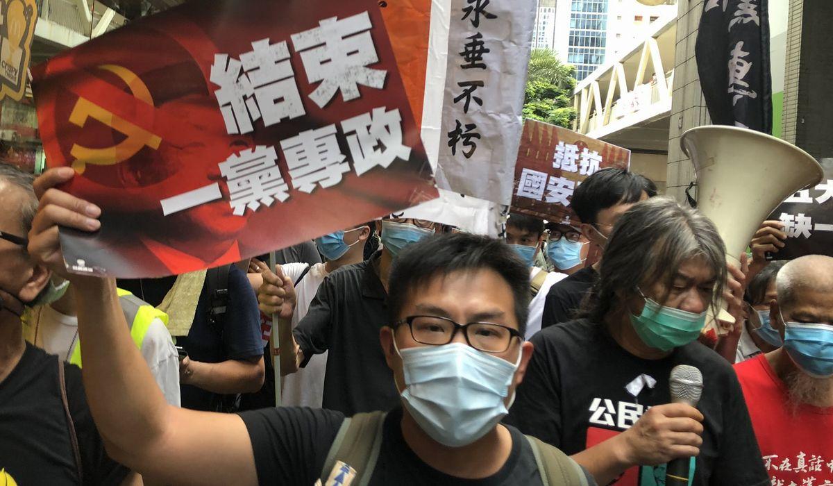 写真・図版 : 香港国家安全維持法の施行に反対する香港のデモ行進で「(中国共産党の)一党独裁を終わらせよ」と書かれたビラを掲げる参加者ら=2020年7月1日