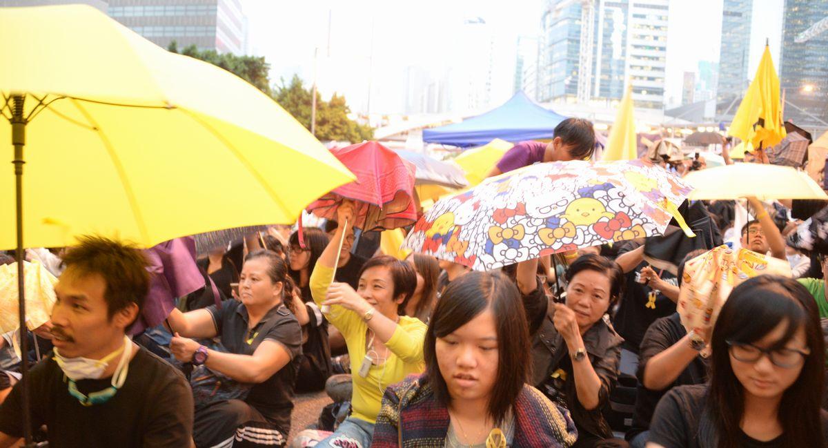 写真・図版 : 2014年の雨傘運動。香港の中心街を占拠して1カ月になるのに合わせてシンボルの傘を一斉に開くデモ参加者ら=香港・金鐘