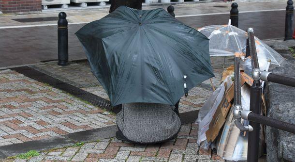 写真・図版 : 川沿いで路上生活をしているという男性。骨の折れた傘で雨風をしのいでいた=2020年6月、東京都内