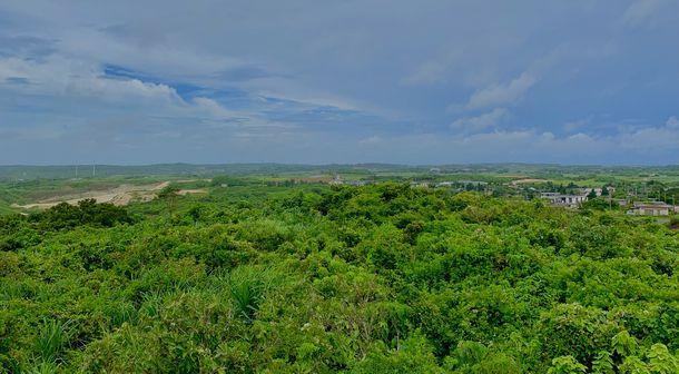 写真・図版 : 左に見える保良鉱山地区で弾薬庫の建設が進んでおり、2021年3月に施設の一部が完成した。右手の集落と最も近いところから約200メートルしか離れていない=2019年6月、沖縄県宮古島市、筆者撮影