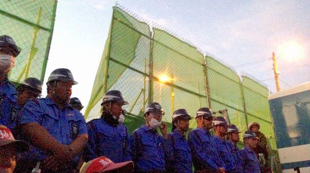 写真・図版 : 辺野古新基地建設に反対する市民に対し、ゲート前で警備にあたる民間警備会社の警備員=2015年11月、沖縄県名護市、筆者撮影