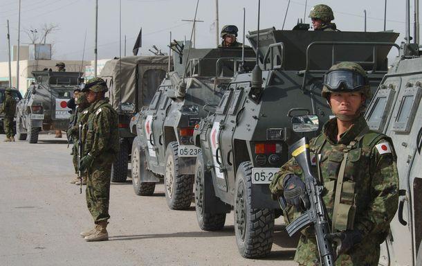 写真・図版 : イラクへ派遣され、移動中に周囲を警戒する自衛隊員。活動は非戦闘地域限定とされたが、戦闘地域ではないかと議論がある地区が拠点となった=2004年3月、サマワ近郊