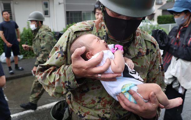 写真・図版 : 九州豪雨の被災地で、自衛隊員に救命ボートで救助された赤ちゃん=2020年7月7日、福岡県大牟田市の上屋敷地区