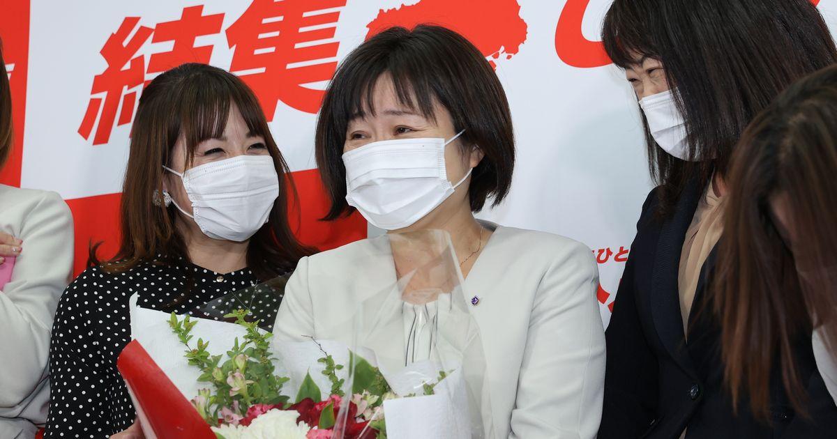 写真・図版 : 参院広島選挙区再選挙で勝利を決め、女性から花束を受け取り、笑顔を見せる宮口治子氏(中央)=2021年4月25日、広島市中区