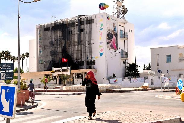写真・図版 : ブアジジの焼身自殺は大規模な民主化運動「アラブの春」にきっかけになり、巨大巨大なモニュメントがビルの壁面を飾るようになった=2018年7月11日、チュニジア・シディブジド