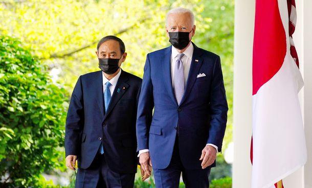 写真・図版 : 日米首脳会談を終え共同会見に臨む菅義偉首相(左)とバイデン大統領=2021年4月16日、ワシントン