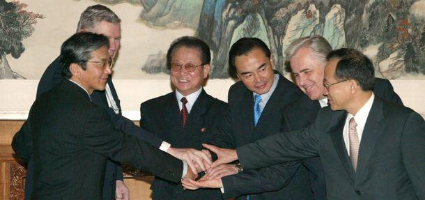 写真・図版 : 初の6者協議を前に握手をかわす各国代表=2003年8月27日、北京・釣魚台国賓館