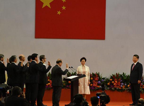 写真・図版 : 香港政府高官ポストへの就任にあたり、中国の習近平国家主席(右)の前で宣誓する幹部ら=2017年7月1日
