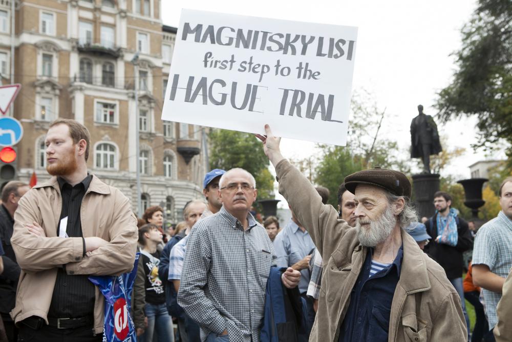 写真・図版 : プーチン大統領に抗議し、マグニツキー法を支持するプラカードを掲げるモスクワ市民=2021年9月15日、モスクワ