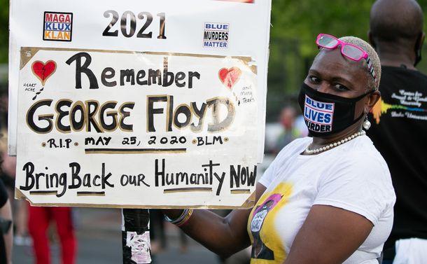 写真・図版 : 白人の元警官有罪の評決を受け、ホワイトハウス近くでジョージ・フロイドさんの名を記したボードを掲げる人=2021年4月20日、米ワシントン、ランハム裕子撮影