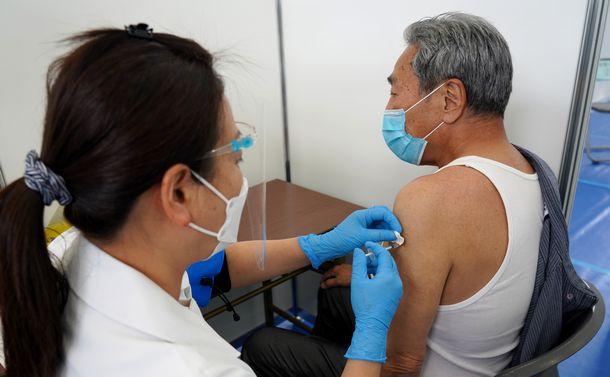 写真・図版 : 新型コロナウイルスワクチンの接種を受ける男性。世田谷区で一般の高齢者向け接種が始まった=2021年5月3日、東京都世田谷区の大蔵第二運動場体育館