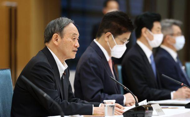 写真・図版 : 新型コロナ感染症対策本部で4都府県の緊急事態宣言延長などを決定したことを伝える菅義偉首相=2021年5月7日、首相官邸