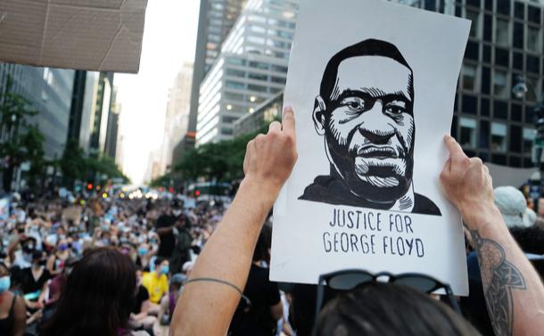 写真・図版 : ジョージ・フロイド氏の似顔絵を掲げて黒人差別に抗議する人=2020年6月10日、米国ニューヨーク、shutterstock.com