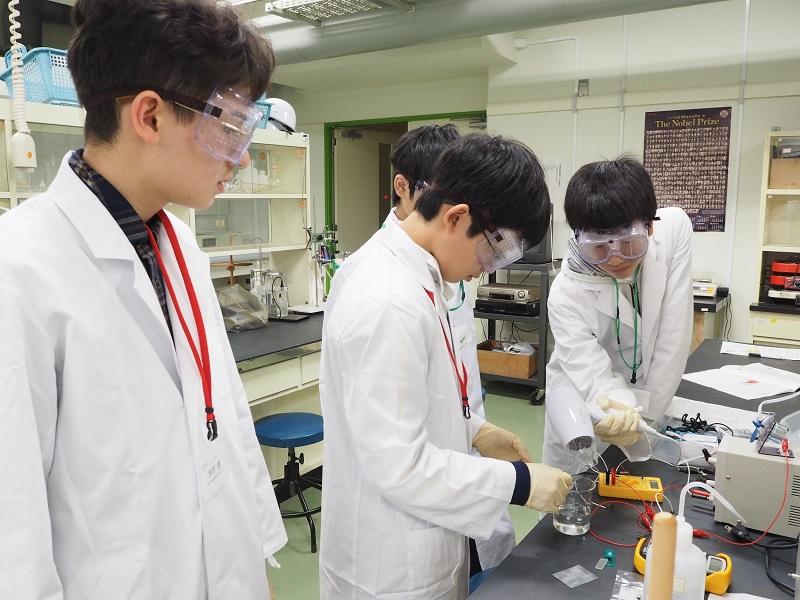 写真・図版 : 筑波大学GFESTでは、毎年ノーベル化学賞受賞者の白川英樹先生による講義と実習がある。写真はその実習の様子。導電性高分子を合成し、二次電池としての機能や性能を調べる=2018年11月4日、筑波大学