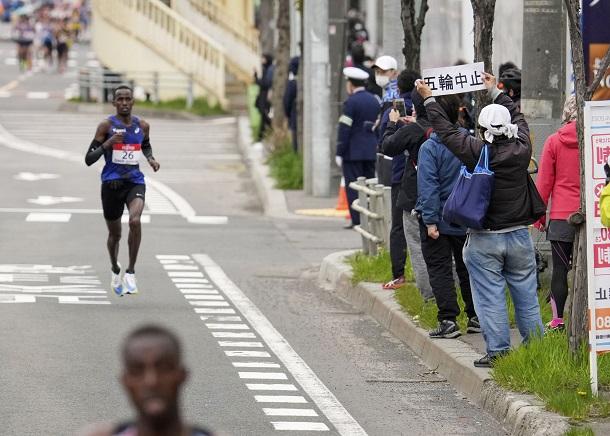 写真・図版 : 「北海道・札幌マラソンフェスティバル」で、「五輪中止」と掲げて沿道に立つ人=2021年5月5日、札幌市