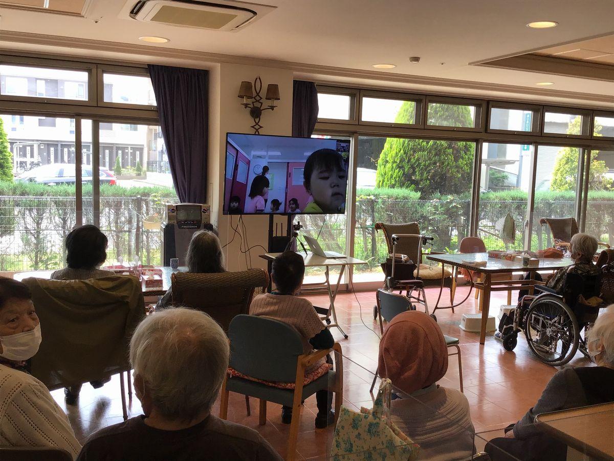 写真・図版 : コロナ禍で直接の交流できなくなった保育園の子どもたちとZOOMで交流する利用者たち(提供写真)
