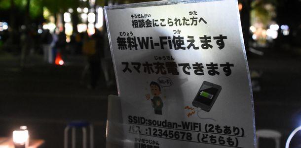 写真・図版 : スマホの利用停止で通話ができなくなった人たちは無料Wi-Fiが命綱になる。「つくろい東京ファンド」は利用者が急している食料支援の会場で無料Wi-Fiや端末の充電コーナーも提供している=2020年11月28日、東京都豊島区東池袋3丁目