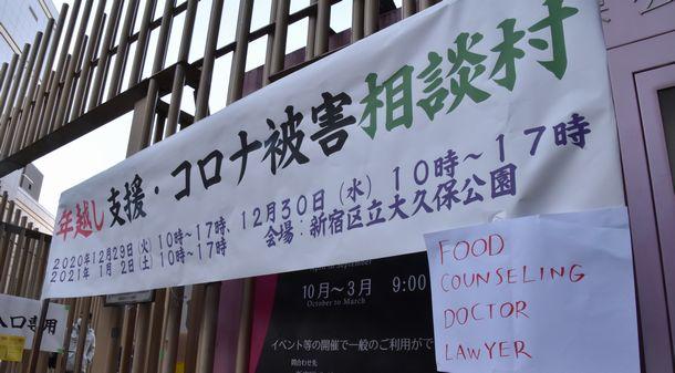 写真・図版 : 会場の出入り口に掲げられた「年越し支援・コロナ被害相談村」の幕。「食べ物、カウンセリング、医者、弁護士」と英語で書かれた案内も張り出された=2021年1月2日、東京都新宿区の区立大久保公園
