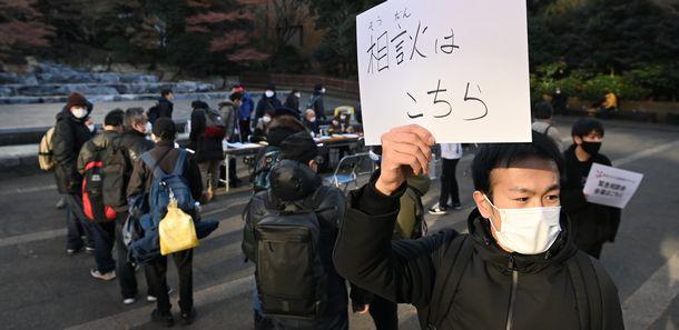 写真・図版 : 仕事や住まいを失って困窮した人のために、約40団体が参加する新型コロナ災害緊急アクションが大みそかに開いた緊急相談会。助けを求めて多くの人々が集まった=2020年12月31日、東京都豊島区の東池袋中央公園