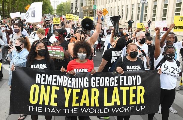 ジョージ・フロイドさんが亡くなってから1年となり、街を練り歩く市民ら=25日、米ニューヨーク20210526