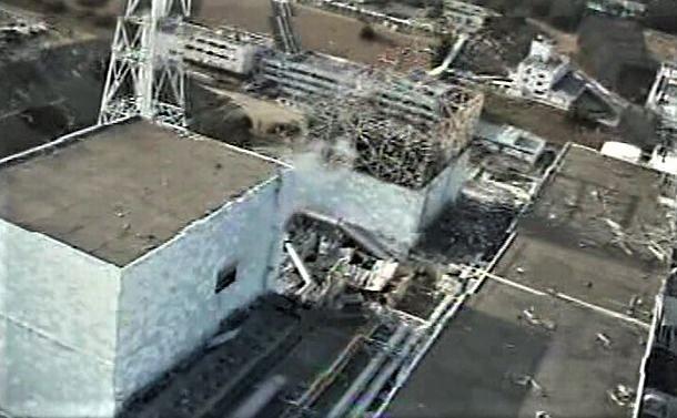 写真・図版 : 福島第一原発2号機(左手前)。原子炉建屋の壁にできた開口部から白煙が出ている=2011年4月10日撮影、翌11日に同社が記者団に提供