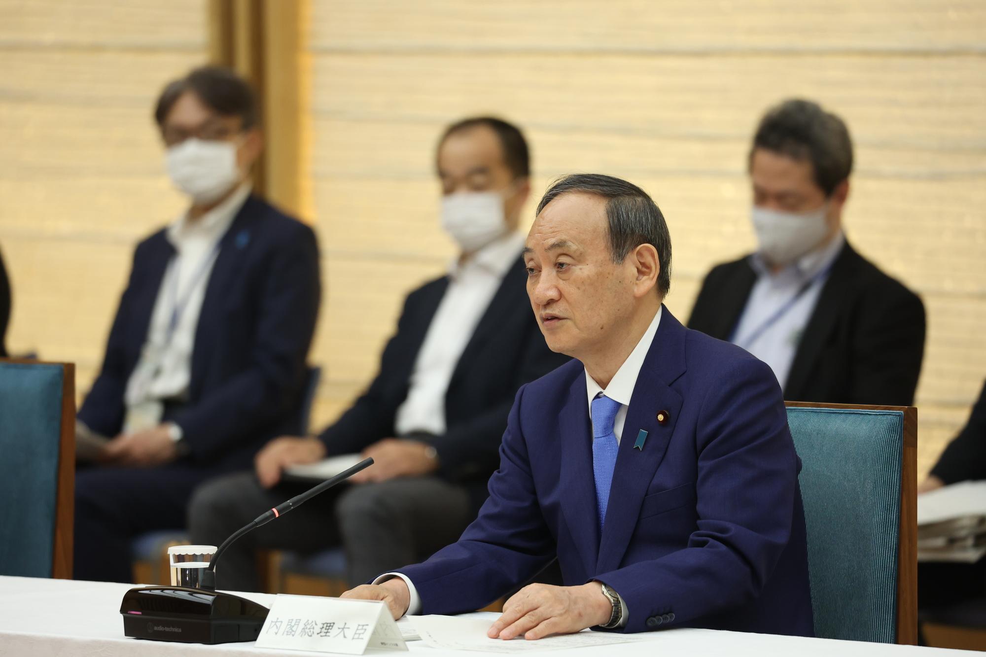 写真・図版 : 新型コロナウイルス感染症対策本部で、沖縄を除く9都道府県の緊急事態宣言の解除を発表する菅義偉首相(2021年6月17日)