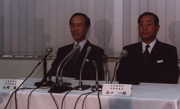 写真・図版 : 辞任を発表する会見に臨んだ北岡社長(左)。右は社長を引き継いだ谷口一郎氏=1998年3月25日、東京・丸の内の三菱電機本社