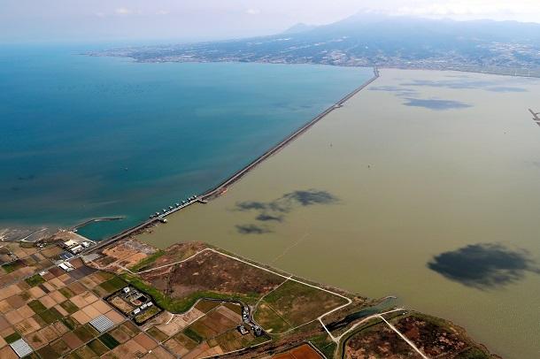 潮受堤防で仕切られた諫早湾。手前は諫早市小長井町、奥は雲仙市=2020年3月、本社ヘリ