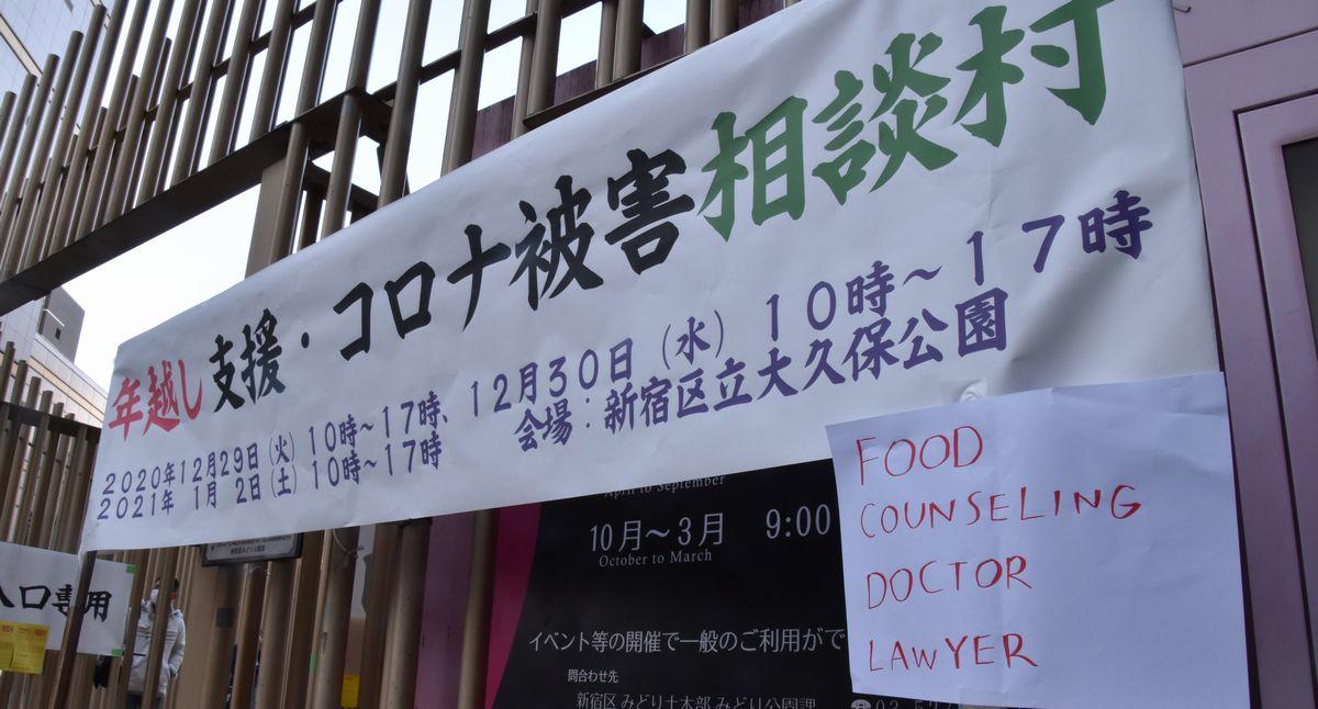 写真・図版 : 「年越し支援・コロナ被害相談村」では、外国人にも相談に来て欲しいと「食べ物、カウンセリング、医者、弁護士」と英語で書かれた案内も張り出された=2021年1月2日、東京都新宿区