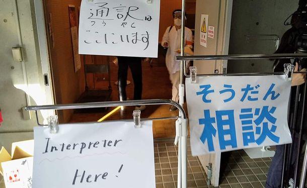 写真・図版 : 今年の「ゴールデンウィーク大人食堂」の相談会場。外国人向けの案内が掲げられた=東京都千代田区、つくろい東京ファンド提供