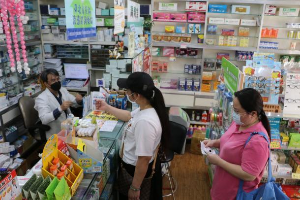 写真・図版 : 買い占めや値段のつり上げを防ぐため、台湾では2月、指定薬局で健康保険カードを示してマスクを購入する仕組みが導入された=2020年2月26日、台北