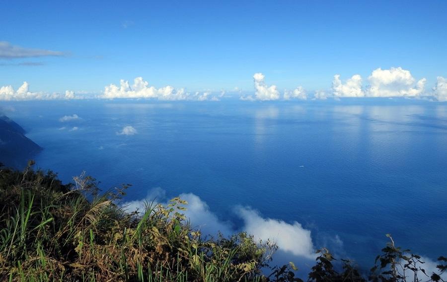 写真・図版 : 台湾の山から眺めた東方の海。雲の切れ間の向こうに与那国島がある。眼では認識できないが、この海には強大な黒潮が流れている=2017年8月、筆者撮影
