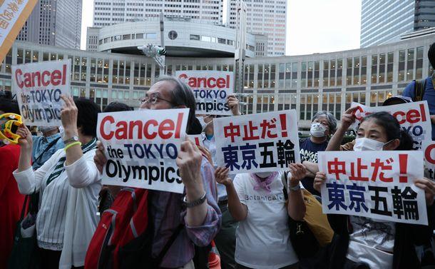 写真・図版 : 都庁前で東京五輪の開催に抗議をする人たち=2021年6月23日、東京都新宿区
