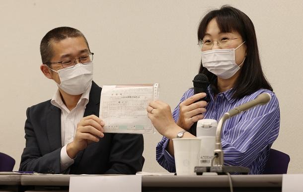 違憲の判断が出た場合に提出しようと思っていた婚姻届を披露する申立人の事実婚カップル=2021年6月23日午後、東京・霞が関20210623