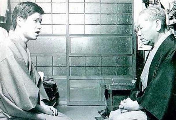 写真・図版 : 八代目林家正蔵(右、「彦六の正蔵」)に、覚えた噺を聞いてもらっている前座時代の林家正雀。演目は「金明竹」で、場所はいわゆる稲荷町の長屋。1974年だという=正雀のツイッターから