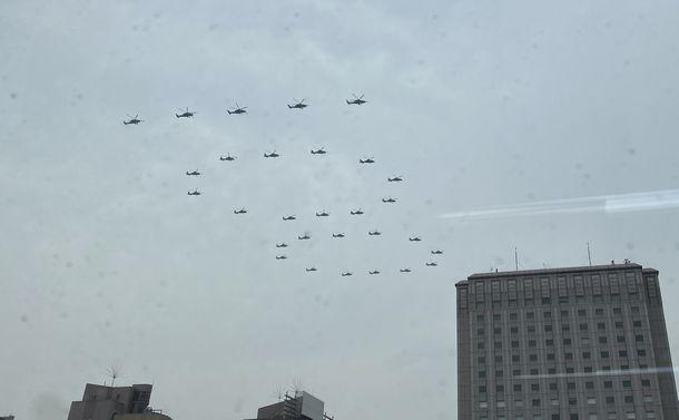写真・図版 : 中国共産党の結党100周年祝賀式典が開かれた天安門広場に向かって「100」の形で編隊飛行するヘリ部隊=2021年7月1日、北京