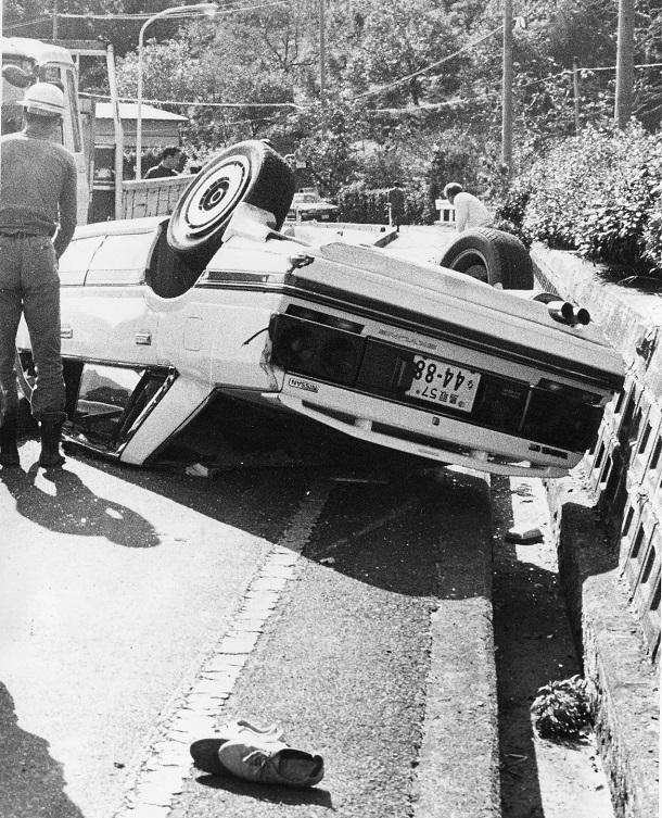 写真・図版 : 3姉妹をなぎ倒したあと、歩道にひっくり返った車=1991年11月2日、鳥取県八頭郡船岡町橋本の県道