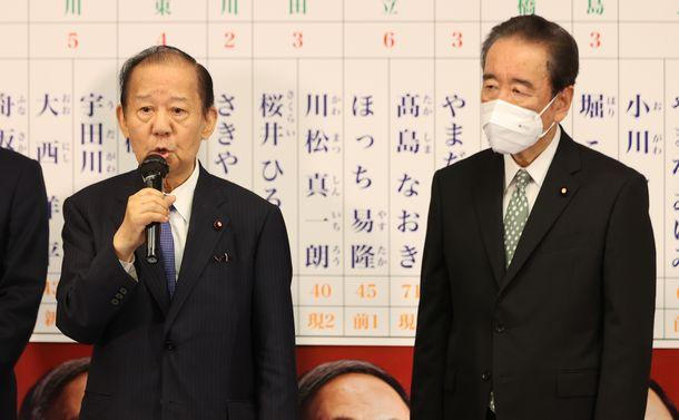 写真・図版 : 都議選の開票が進むなか、自民党本部の開票センターであいさつする二階俊博幹事長。右は鴨下一郎・東京都連会長=2021年7月4日、東京・永田町