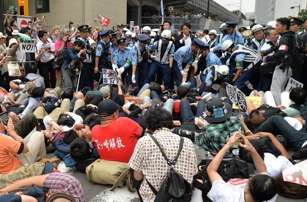 写真・図版 : 安保関連法案の地方公聴会終了後、関係者の車両の進行を妨げようとした市民を排除する神奈川県警の警察官=2015年9月、横浜市