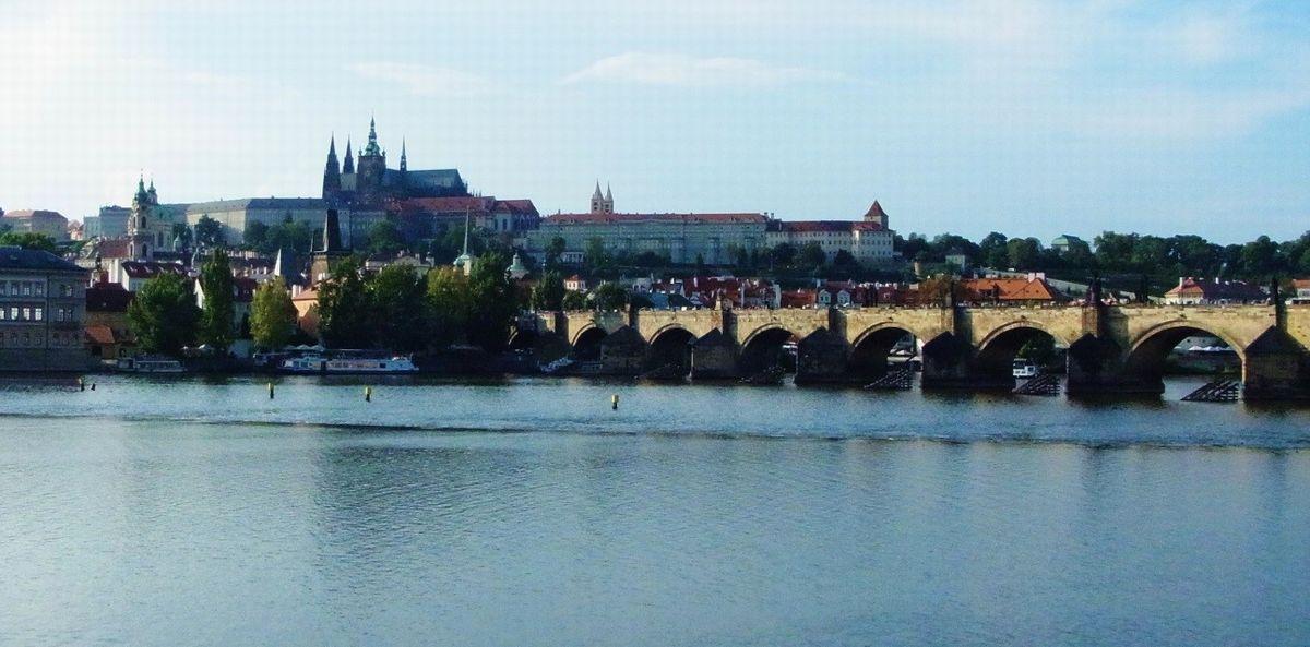 写真・図版 : 歴史的な町並みを巡るプラハのオンラインツアー。正面のプラハ城を出て、ヴルタヴァ川にかかるカレル橋を渡り旧市街地を行く=筆者撮影