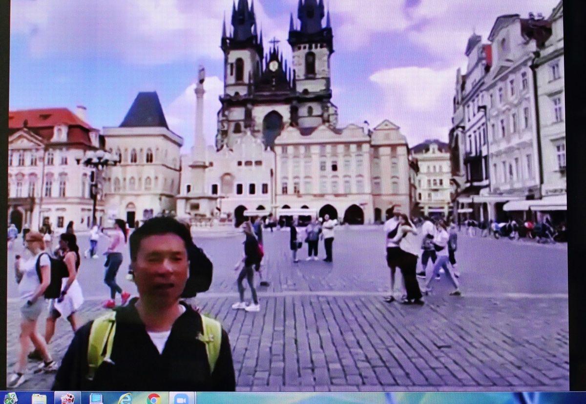 写真・図版 : パソコン画面にライブ映像で映るプラハの旧市街広場とガイドの細矢元洋さん。オンラインツアーは6月下旬に行われたが、マスク無しの観光客の姿が見られる=筆者撮影