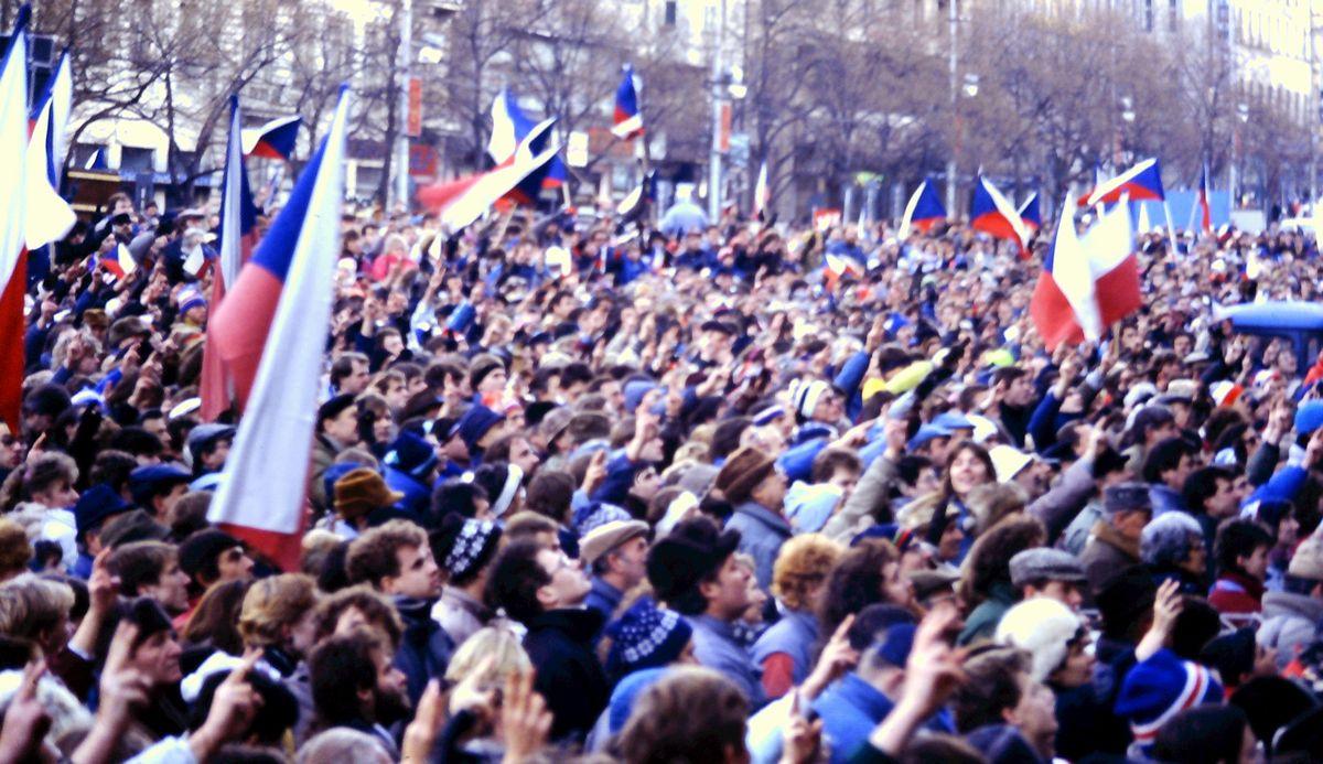 写真・図版 : チェコの革命勝利を祝うプラハでの30万人集会。市民たちは腕を伸ばしてVサインを掲げた=1989年12月10日、筆者撮影